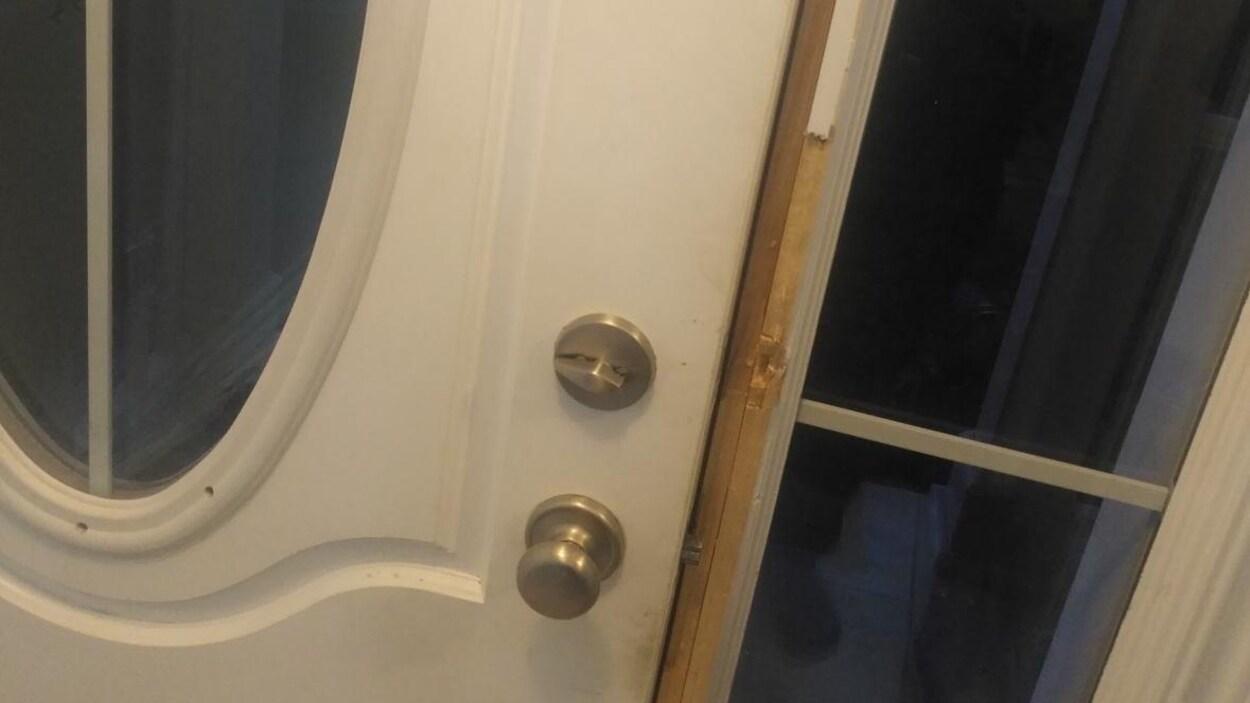 Un porte de maison dont le cadre a été défoncé.