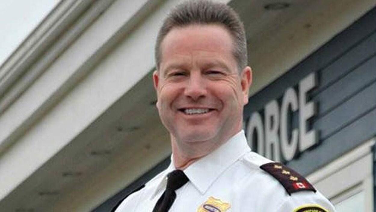 Jeff Porter souriant devant le poste de police