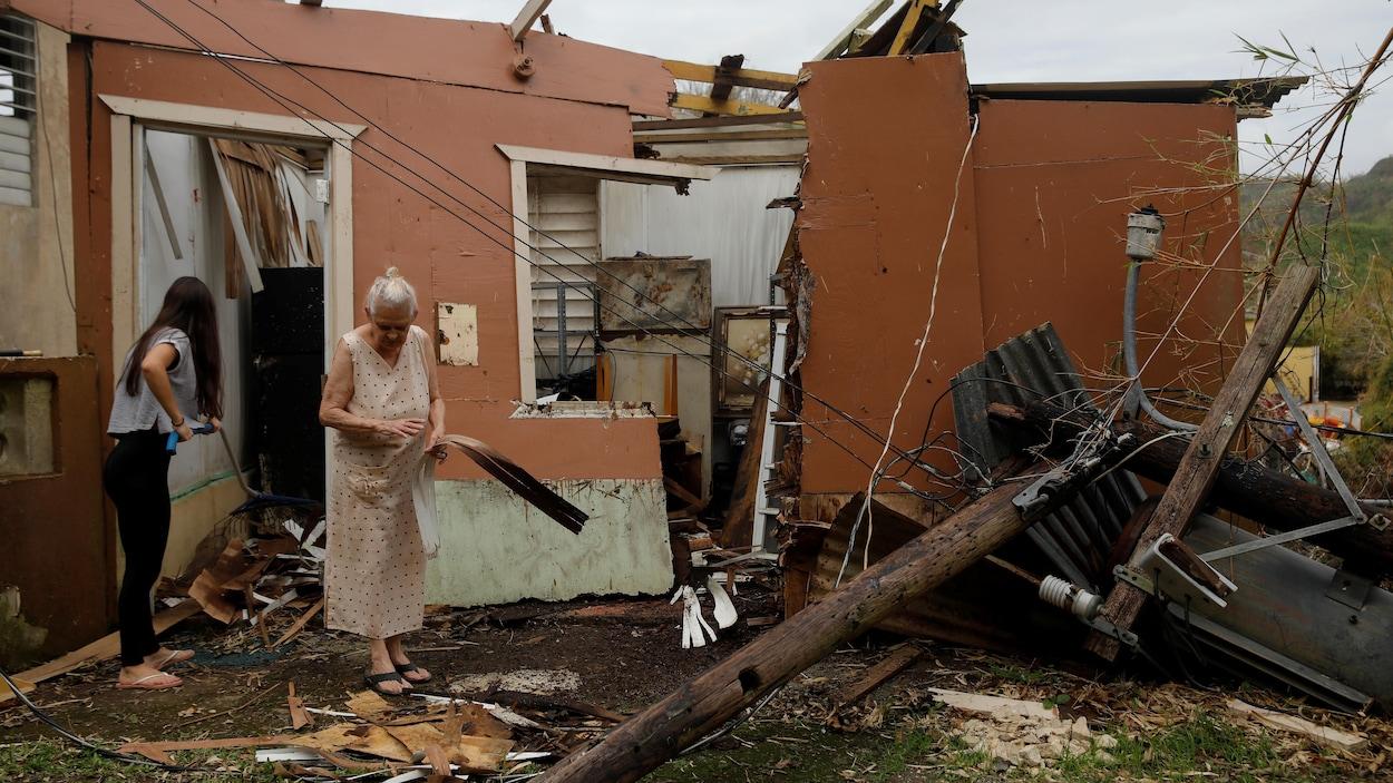 Deux femmes tentent de trier les débris de leur maison, réduite à l'état de ruines par l'ouragan Maria.
