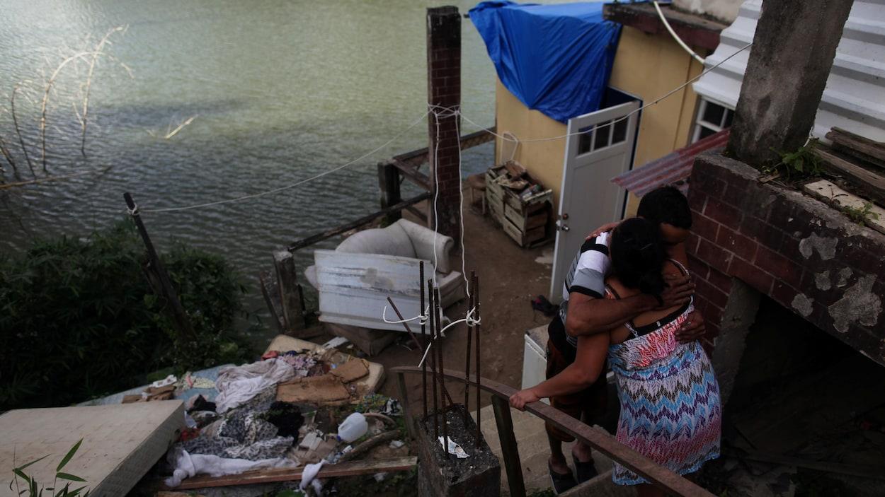 Juan Cosme enlace sa femme dans les ruines de leur maison sur le bord de l'eau.