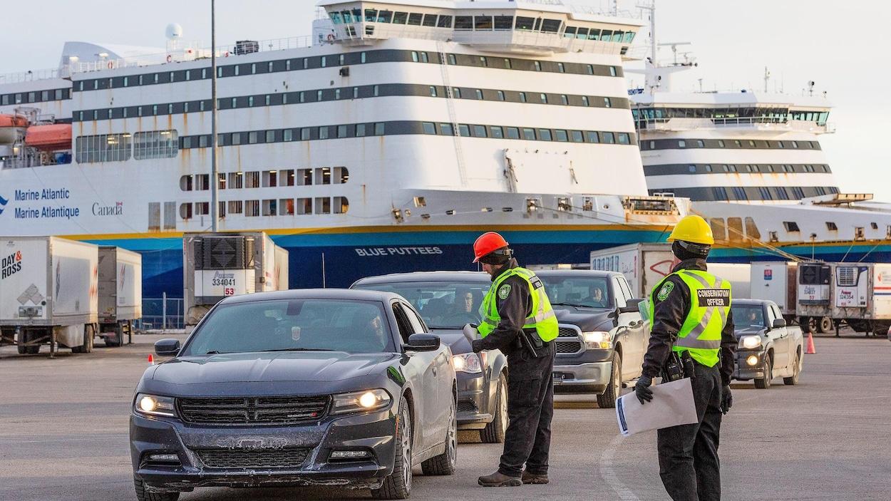 Des agents vêtus de vestes jaunes s'approchent des automobiles qui sortent du traversier amarré au quai.