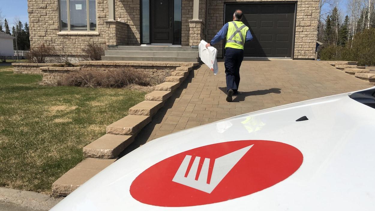Un facteur s'apprête à déposer un colis devant la porte d'une maison.
