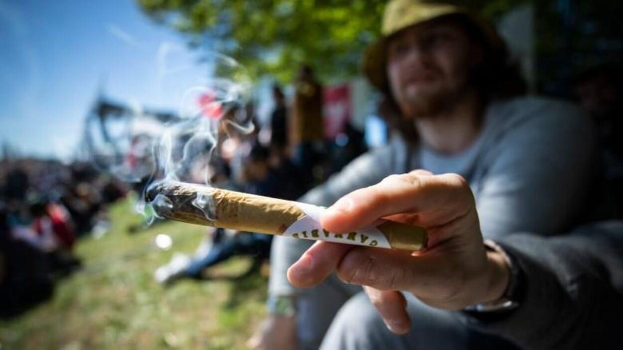 Une main tient un gros joint avec de la fumée et un jeune homme en arrière-plan et hors focus.