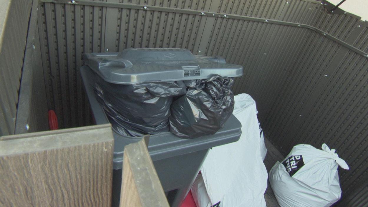 Un bac gris rempli avec deux sacs blancs posés à côté.