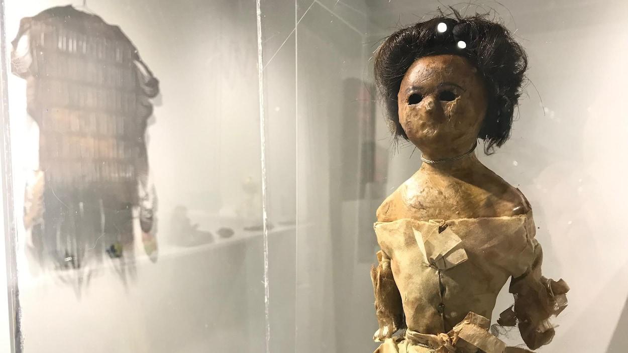 Une poupée de cire avec une robe et des cheveux bruns hmains dans une vitrine.
