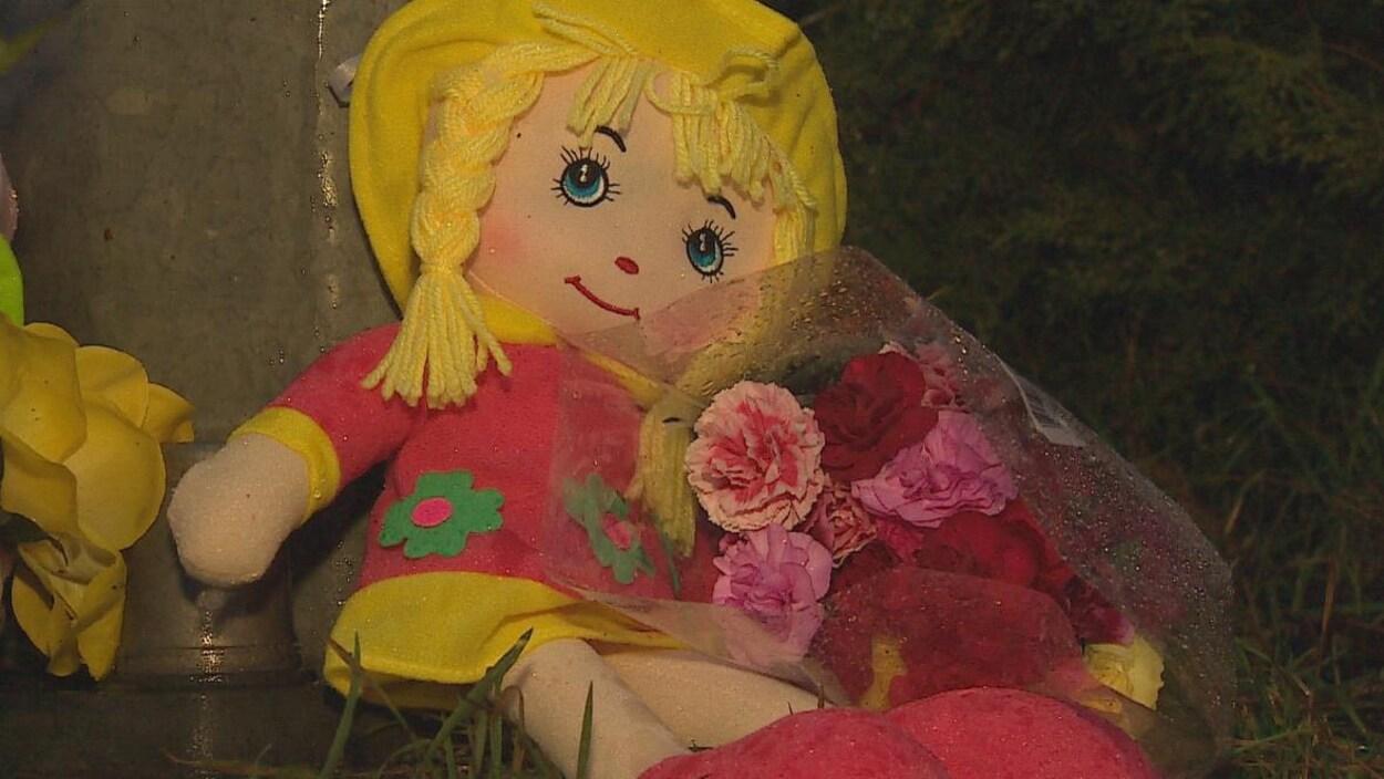 Une poupée aux cheveux blonds tient des roses au bord d'une route.