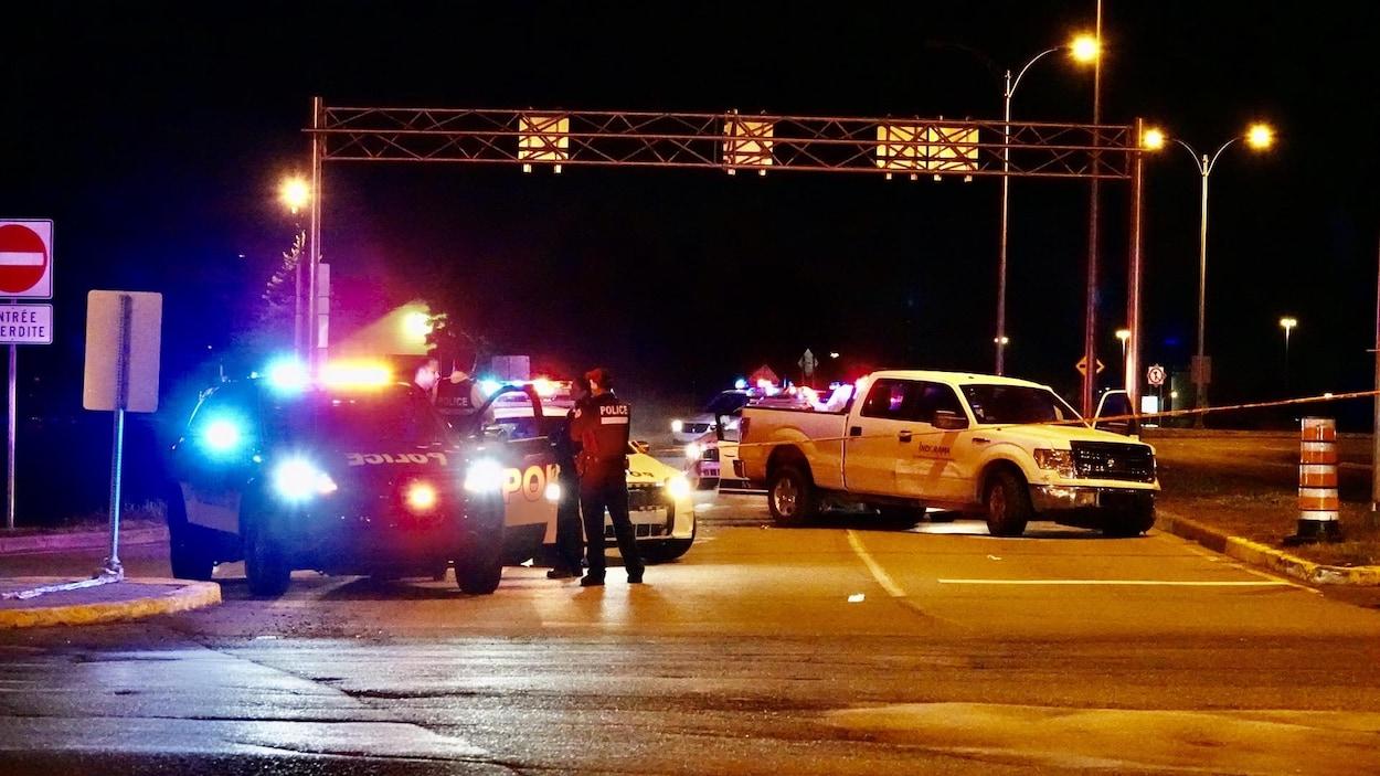 Des voitures de police et une camionnette accidentée, la nuit.