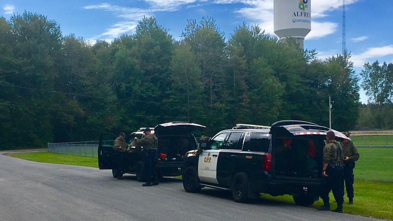Des policiers autour de deux voitures de la PPO.
