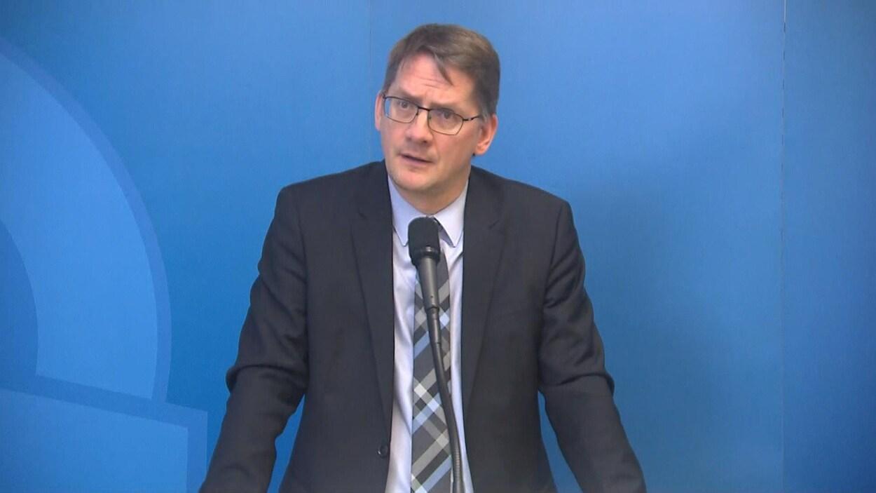 L'homme fait face à un micro lors d'une conférence de presse