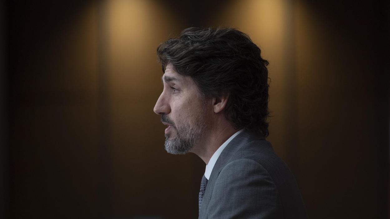 Justin Trudeau vu de profil dans une pièce sombre.