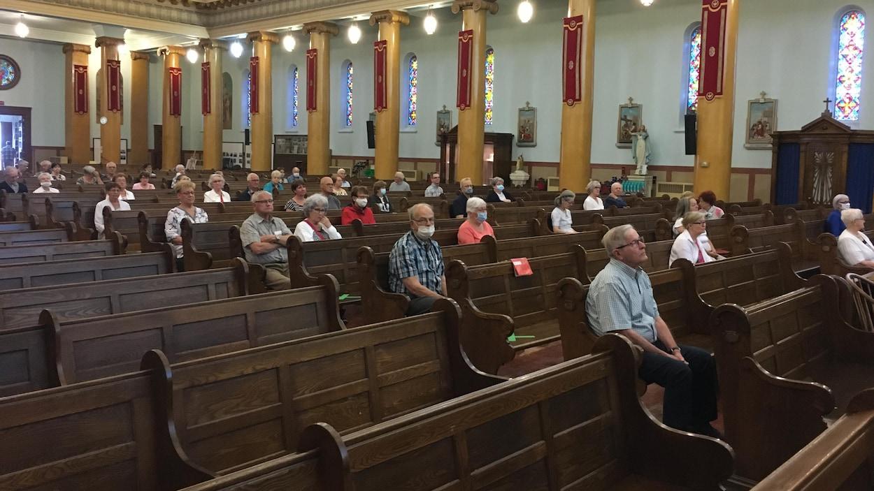 Une foule avec deux mètres de distance dans une église.