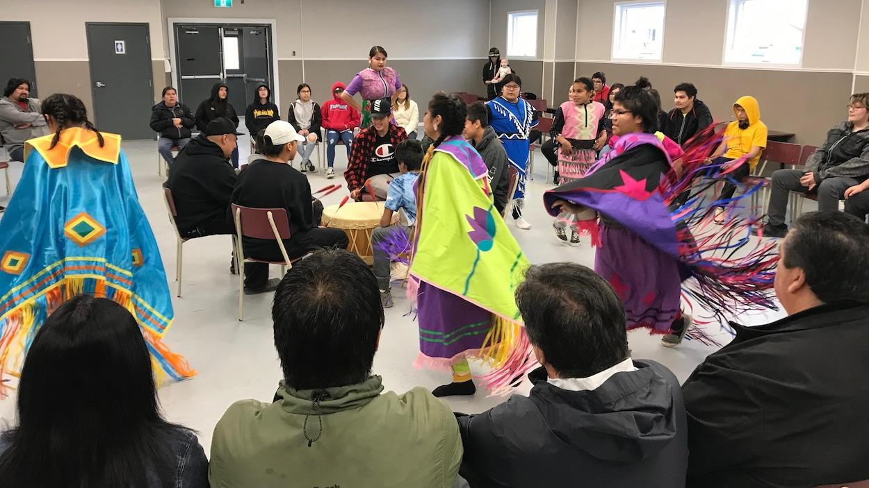 Des enfants portant des tenues traditionnelles autochtones dansent autour de jeunes jouant du tambour.