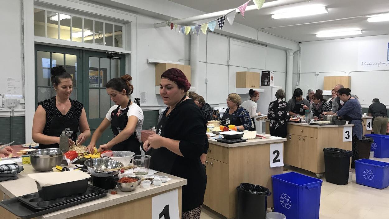 Des femmes travaillent à faire de la nourriture sur des îlots de cuisine.