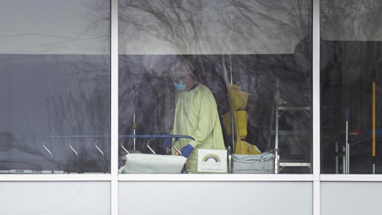 Un homme masqué portant des gants et une blouse jaune lave une civière.