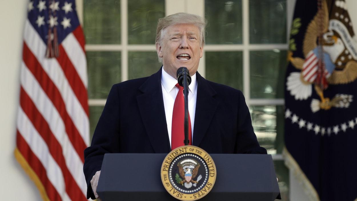Donald Trump parle au micro derrière un podium portant le sceau présidentiel.