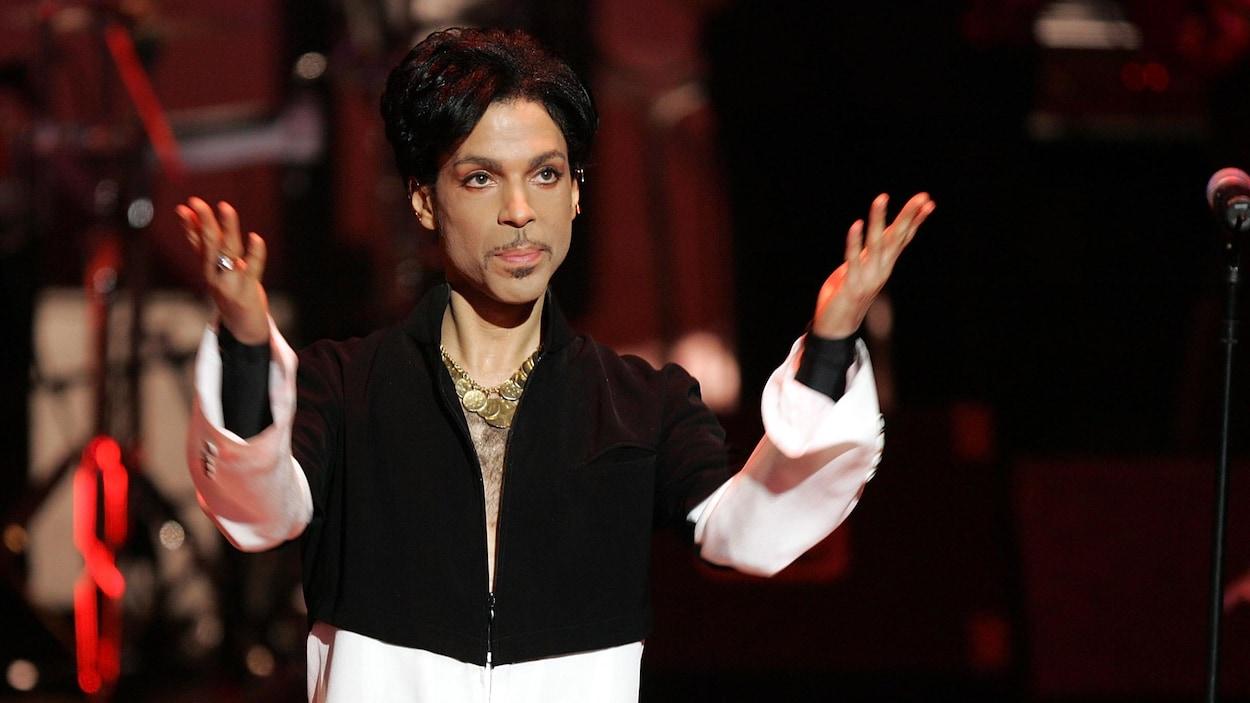 Le musicien Prince lève ses mains vers le ciel alors qu'il se tient sur scène lors d'un spectacle.