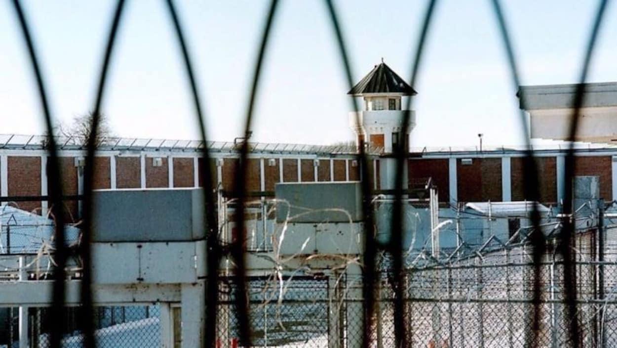 Vue d'un centre carcéral au travers des grilles de sécurité qui l'entourent.