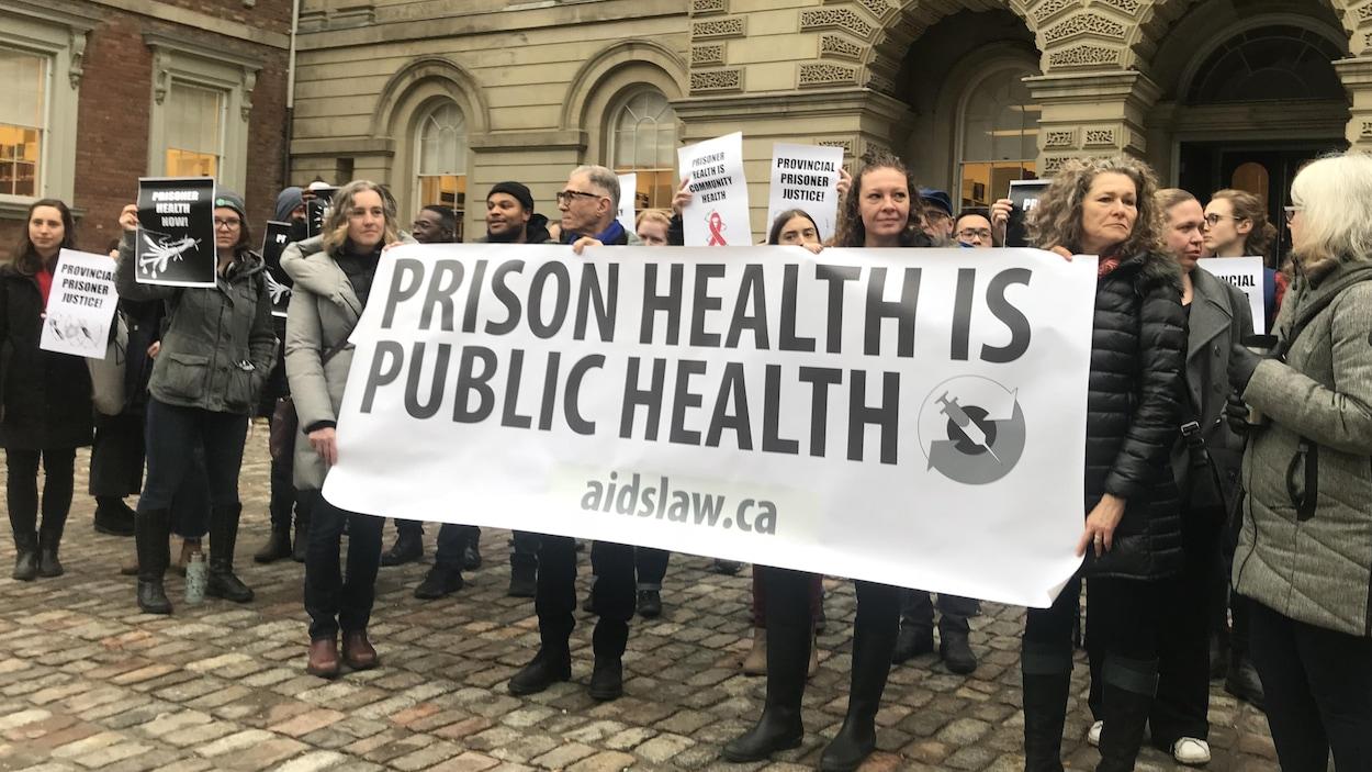 Un groupe de personnes tenant une bannière et des pancartes.