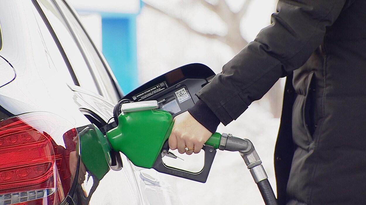 Une main de femme tient une pompe à essence verte.