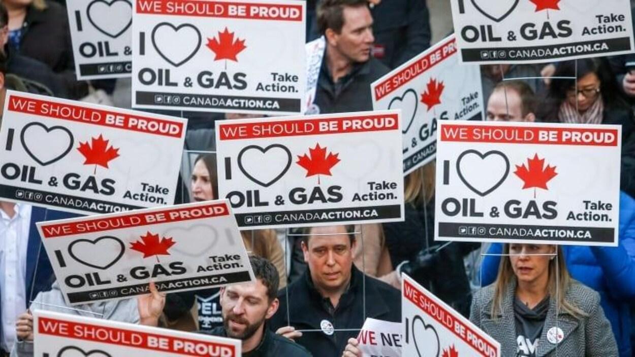 Une foule de manifestants brandit des pancartes indiquant en anglais: « we should be proud » et « I love oil and gas ».