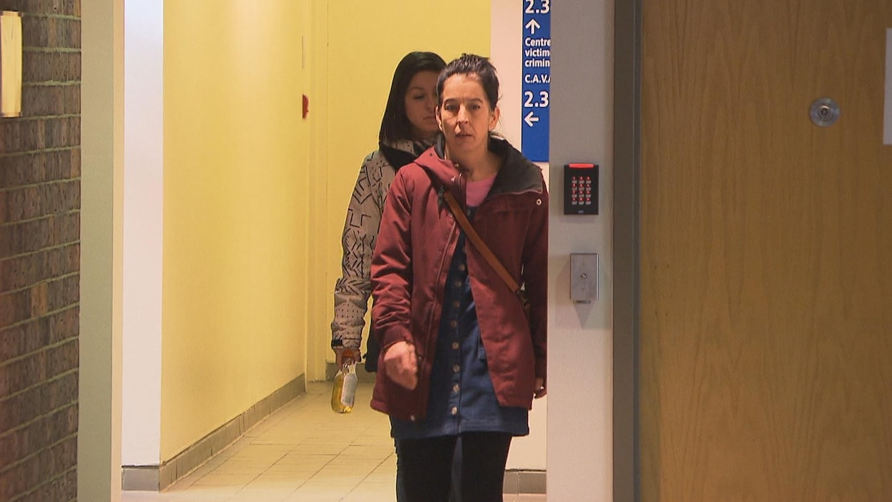 Deux femmes qui marchent dans un couloir du palais de justice.