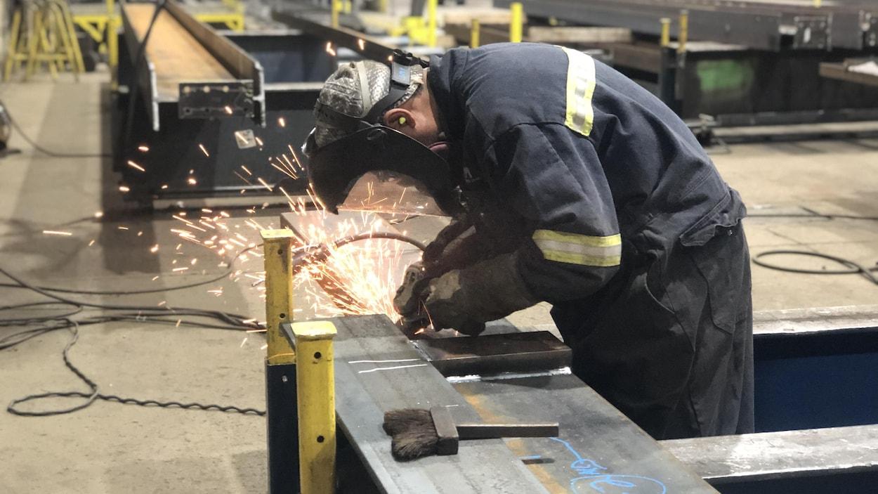 Le travailleur est en train de souder une pièce d'acier dans une usine.