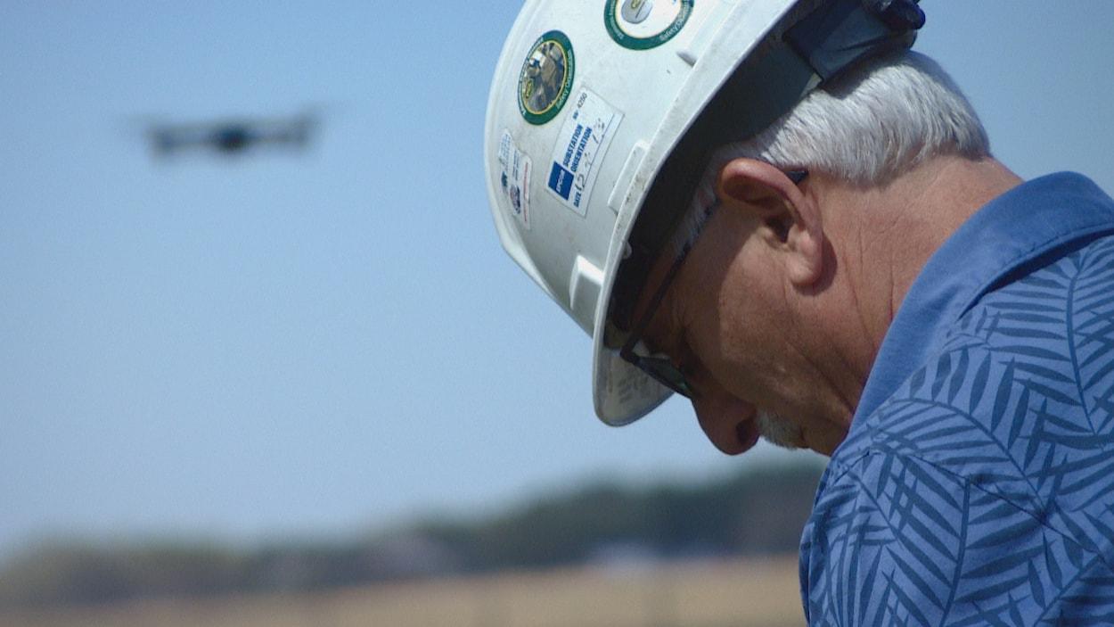 Tom Dudley, pilote professionnel, avec un casque sur la tête en train de piloter un drone dans un champ près d'Edmonton.