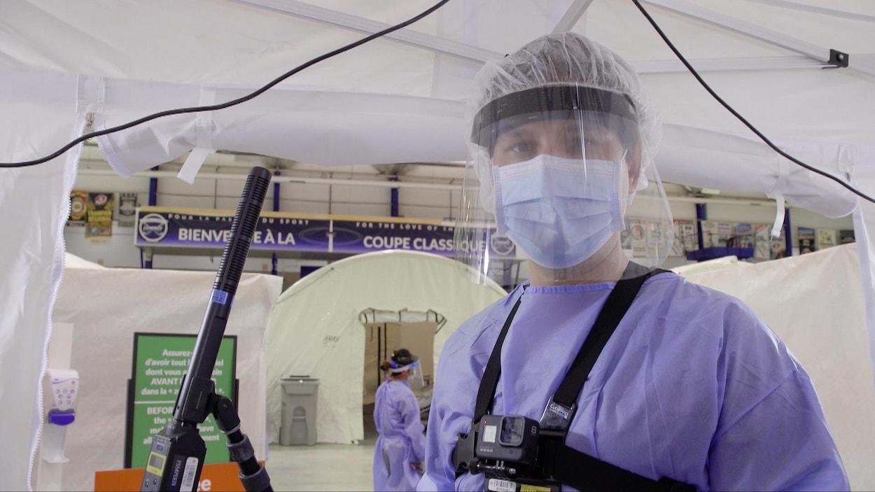 Un homme portant des équipements de protection individuelle (ÉPI) pour dépister la COVID-19.