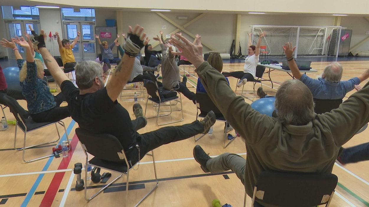 Des hommes et des femmes assis sur des chaises dans un gymnase lèvent les bras et les jambes.