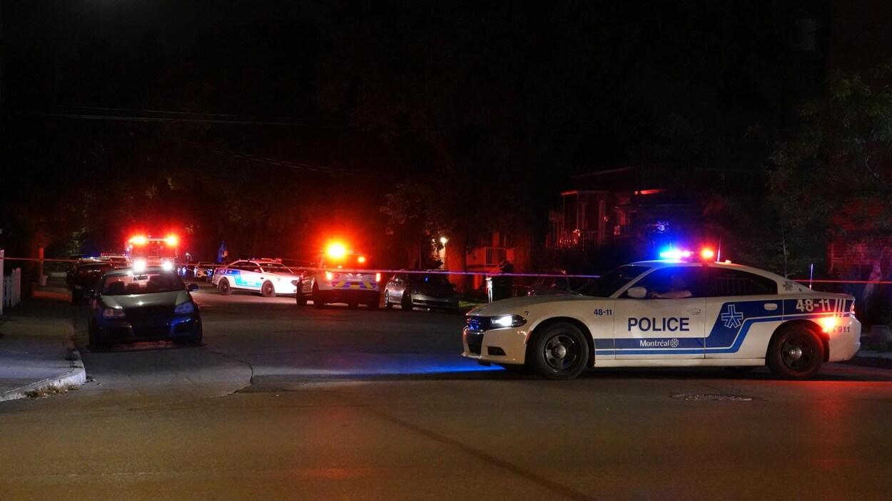 Des voitures de police et un périmètre de sécurité, établi devant l'appartement de la victime.