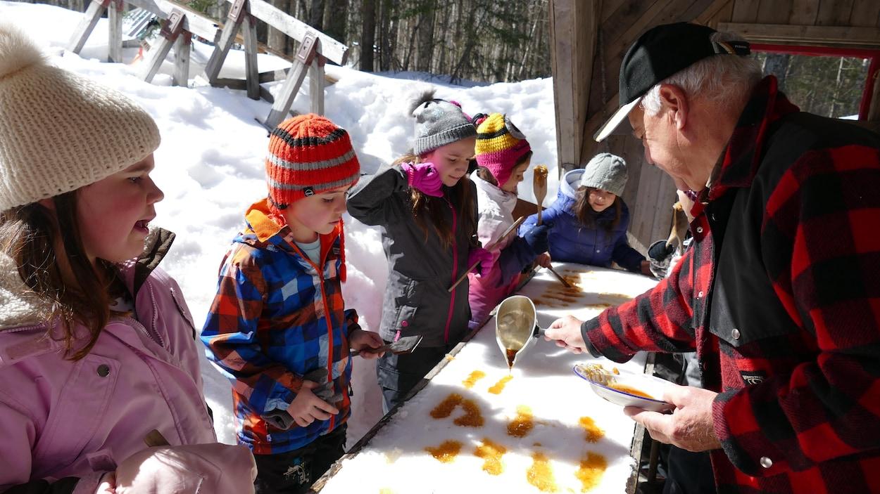 Des enfants qui mangent de la tire d'érable qu'un homme âgé étend sur la neige.
