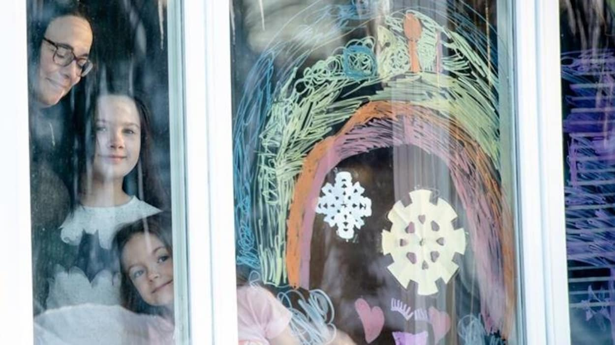 À la fenêtre d'une maison, une maman avec ses deux filles sourient. Un arc-en-ciel est dessiné dans la fenêtre.