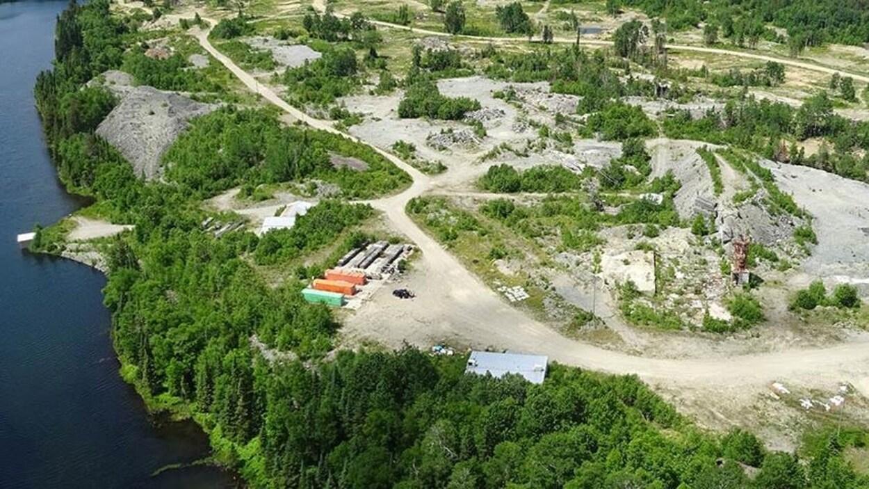 Vue aérienne d'une installation d'exploration minière en forêt près d'un lac.