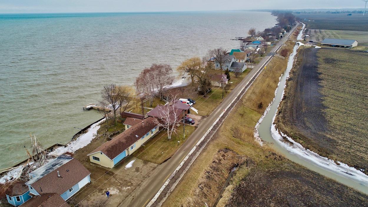 Vue aérienne d'une route. D'un côté, des maisons donnent sur un lac; de l'autre, il y a des terres agricoles.
