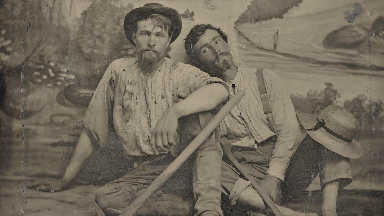 C'est une photo ancienne montrant les deux hommes assis par terre, dans leurs vêtements de prospecteurs, devant une tapisserie de studio de photo. Ils ont l'air sales et plutôt fatigués.