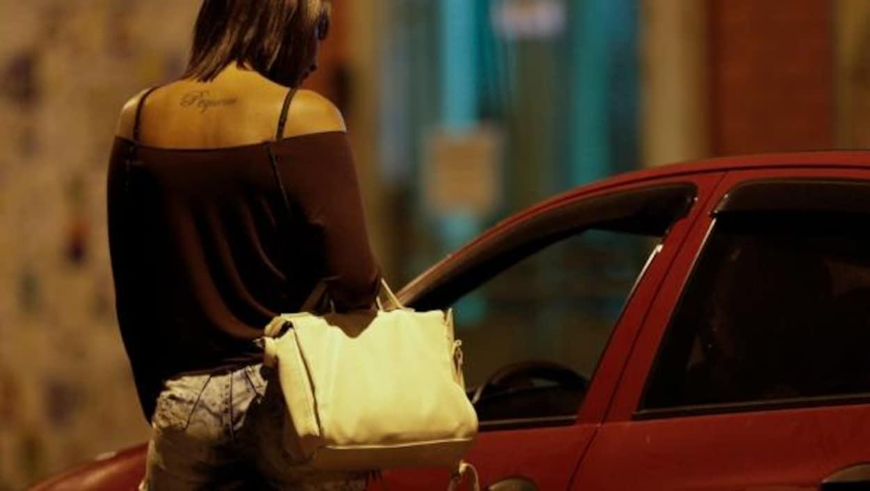 Une femme aux vêtements révélateurs discute avec l'occupant d'une voiture.