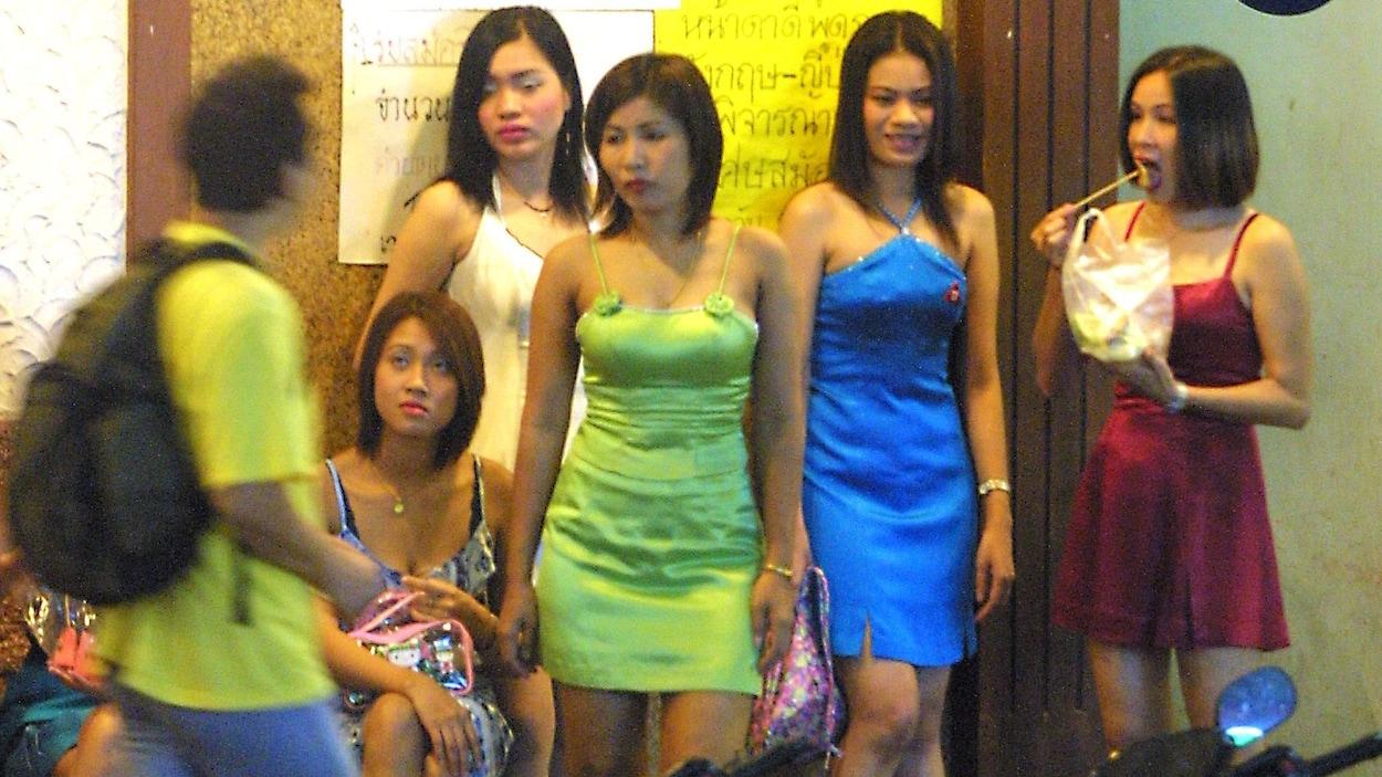 De jeunes prostituées se tiennent devant un bar à Bangkok, en Thaïlande.