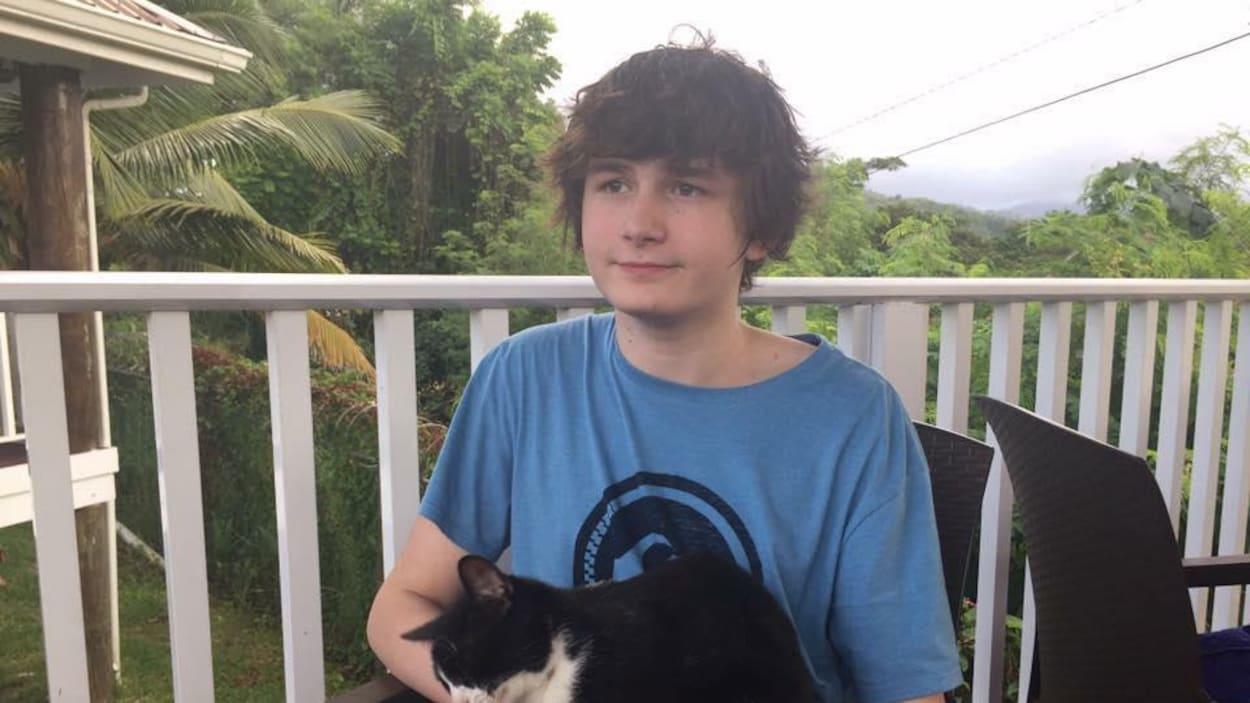 Matthew regarde au loin, un chat assis sur ses genoux.