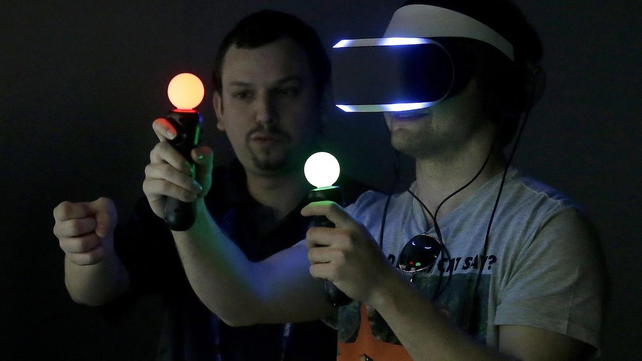 Un homme joue à un jeu en réalité virtuelle avec des manettes contrôlées par le mouvement.