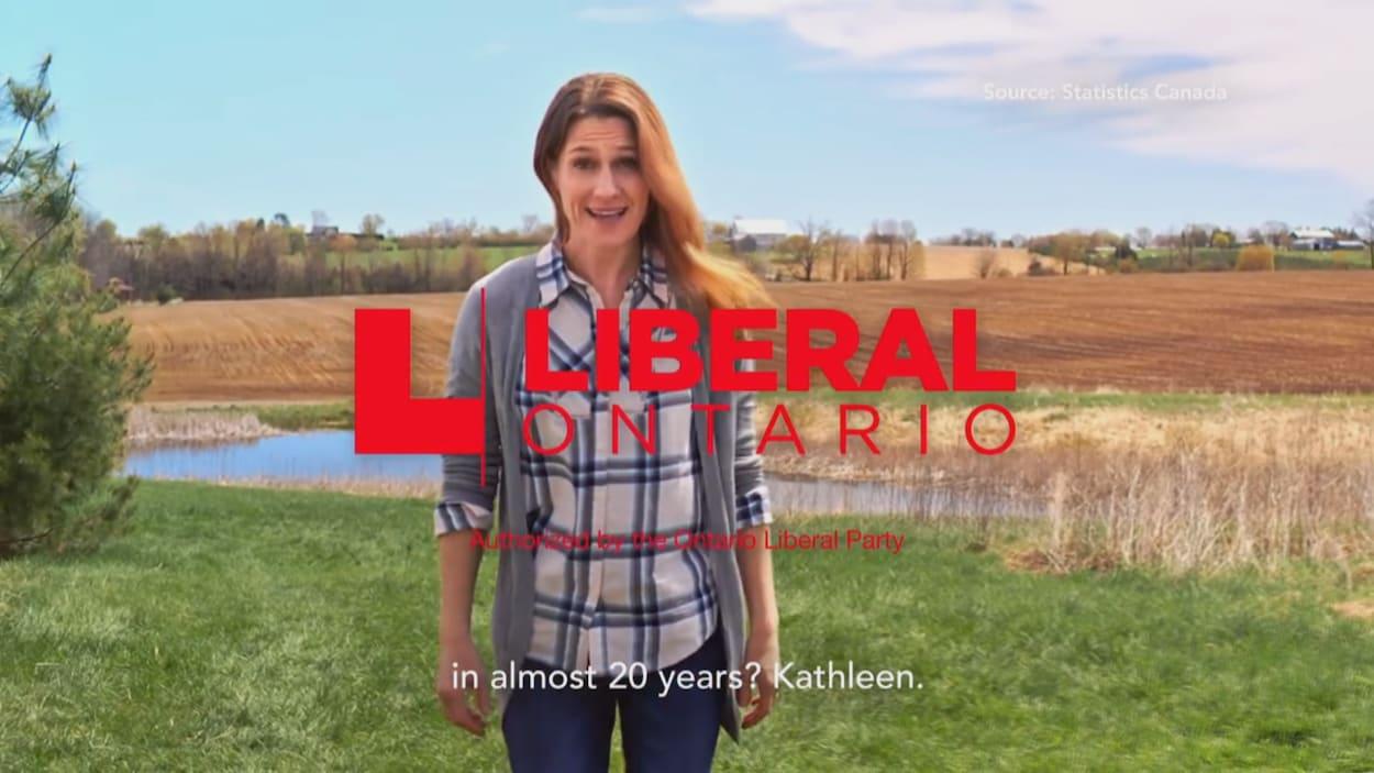 Image de la publicité télévisée. Une femme en jeans et chemise à carreaux marche dans un champ en région rurale.