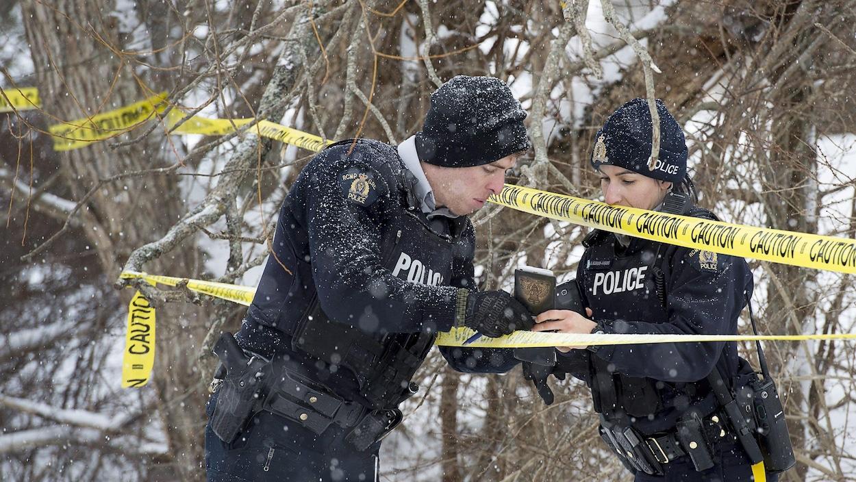 Des policiers consultent des notes sur une scène d'incendie.