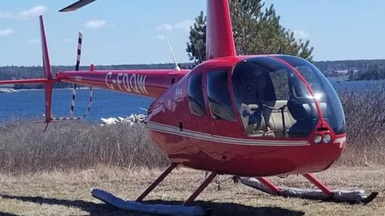 Un petit hélicoptère rouge immobile dans la cour.