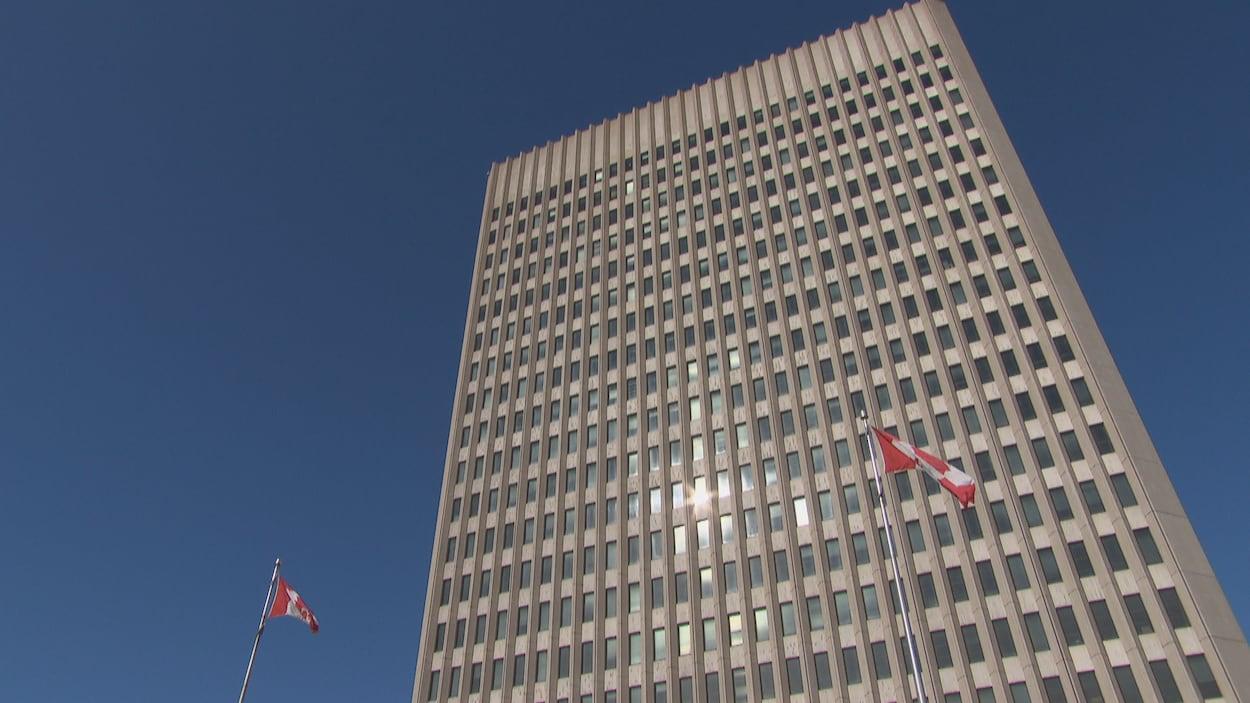 Deux drapeaux du Canada flottent devant une tour à bureaux du gouvernement fédéral à Ottawa.