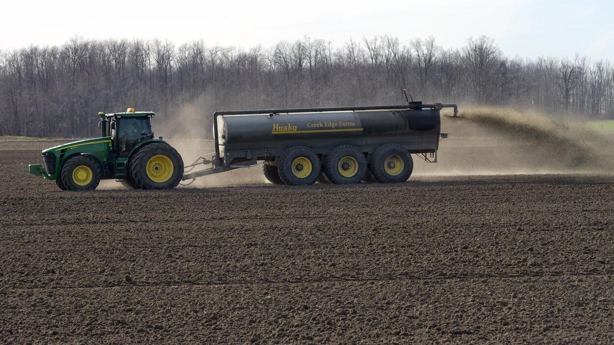 Un imposant tracteur John Deere déversant du lisier dans un champ.