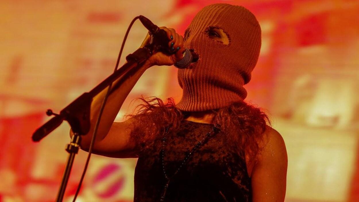 Une femme portant une cagoule chante dans un microphone.