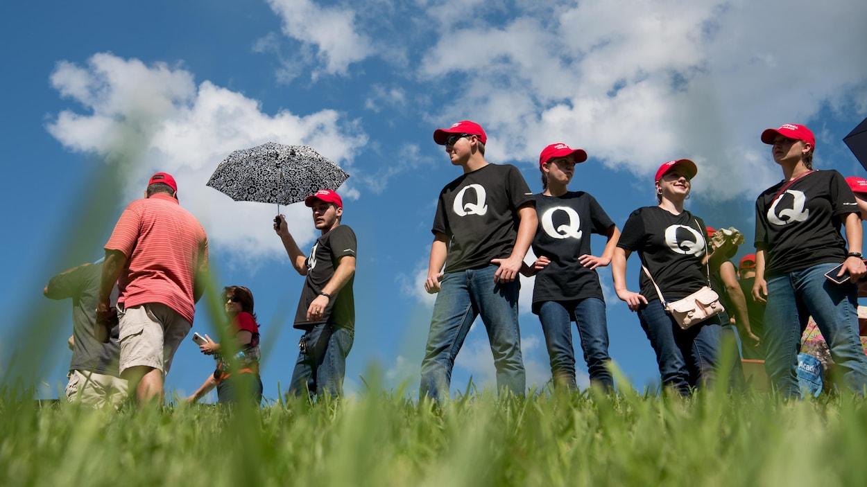 Un groupe de personnes portant des casquettes « MAKE AMERICA GREAT AGAIN » et des t-shirts noirs avec une grosse lettre Q, représentant la mouvance conspirationniste QAnon.