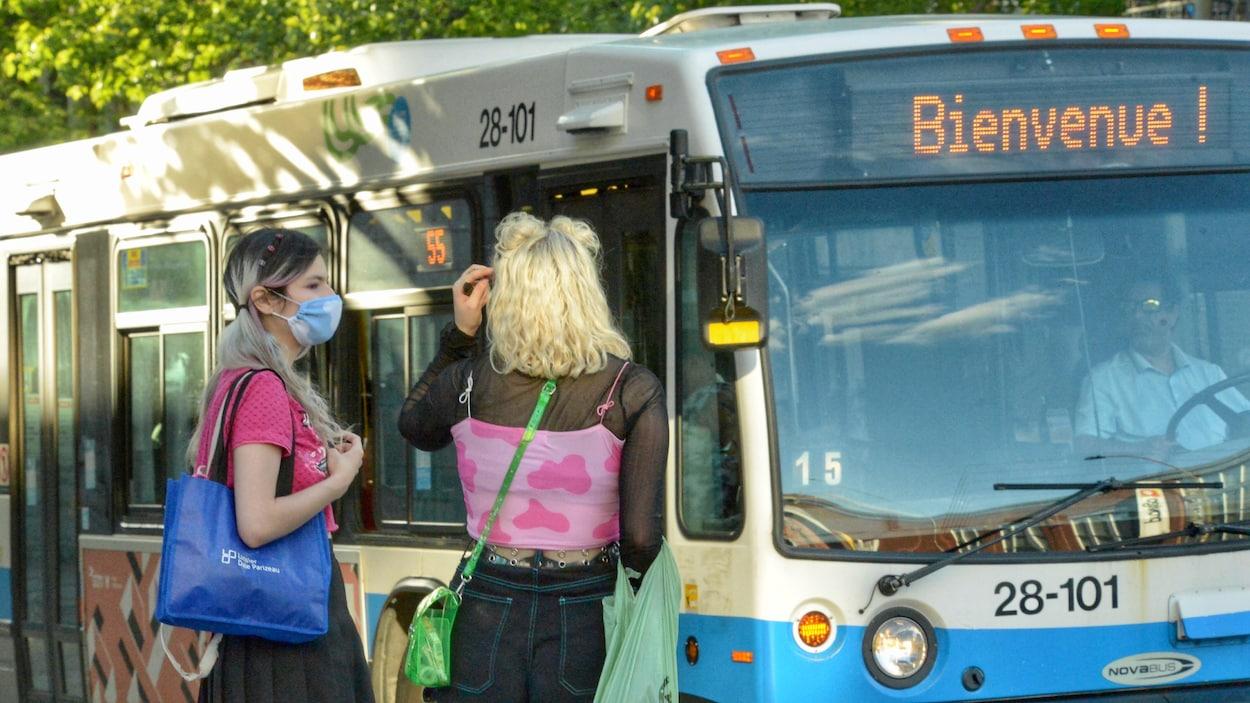 Deux femmes, dont une porte un masque, s'apprêtent à montre dans un bus.
