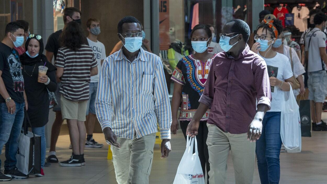 Des personnes portant des masques marchent dans un centre commercial.