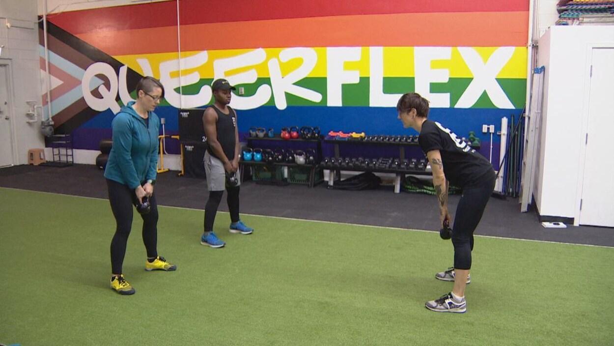Trois personnes s'entraînent avec des poids sur un tapis imitant de l'herbe, devant un mur arborant le drapeau arc-en-ciel sur lequel est écrit Queerflex, le nom du gym.