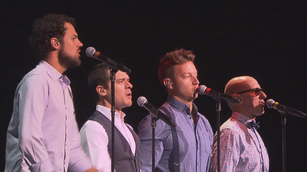 Les membres du groupe chantent au micro